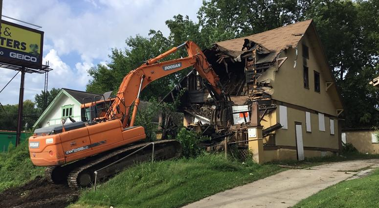 A backhoe uses its bucket to smash through the roof of a burned out home
