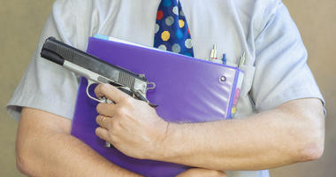Teacher holding a binder and gun