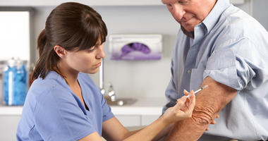 Health care worker administers flu vaccine with hypodermic needle in man's arm