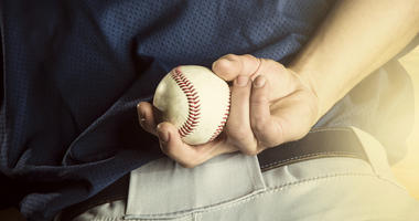 Pitcher holds a baseball behind his back