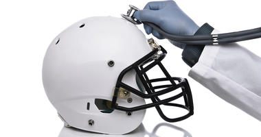 Doctor holds stethoscope to football helmet