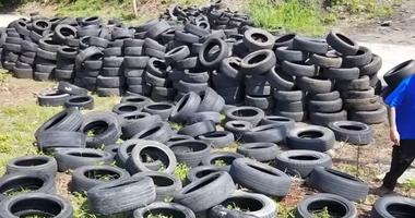 Kansas City illegal dumping investigator walks through a lot containing thousands of tires