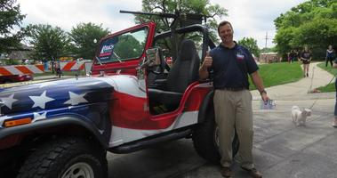 Kris Kobach stands smiling next to his patriotic-styled Jeep that has a replica machine gun mounted to it. He's giving the camera a thumbs up.