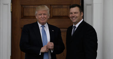 President Trump stands smiling next to Kris Kobach outside the White House