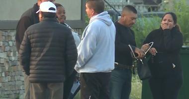 People wait for news outside bar where nine people were shot in Kansas City, Kansas