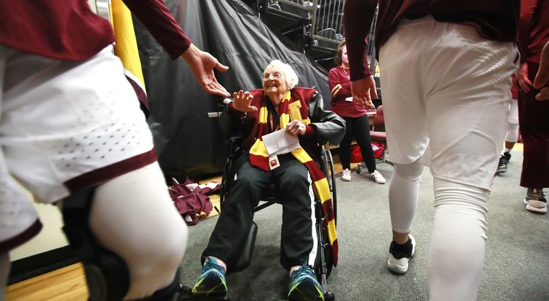 Loyola Ramblers team chaplain, Sister Jean Dolores Schmidt, 98, high fives Loyola players,