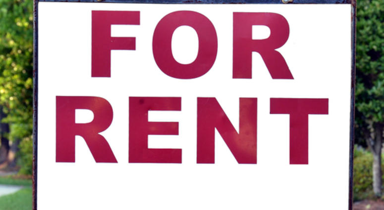 For rent sign on the yard in front of a house