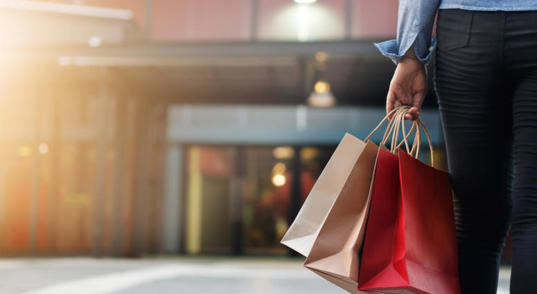 Woman walking with shopping bags on shopping mall background.