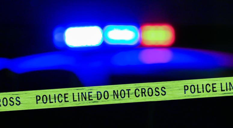 police lights shine behind crime scene tape