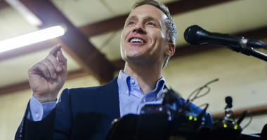 "Missouri Gov. Eric Greitens cheers on a crowd after several protestors were removed from the building before a ceremonial signing making Missouri a ""right-to-work"" state"