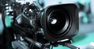 Large professional black video camera filming TV