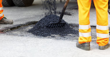 Workmen spreading asphalt to repair a pothole in a roadway.