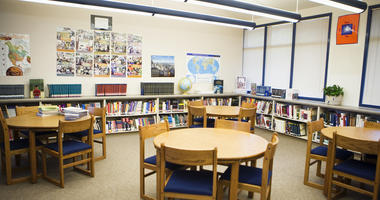 Tables and chairs with book shelves arranged in high school library