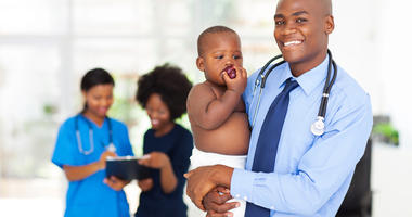 doctor holding baby with mother and nurse on background