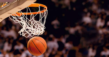 An action photo of a basketball going through the basket of a live game. Scoring points