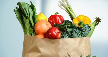 Assortment of fresh produce in grocery paper bag by window