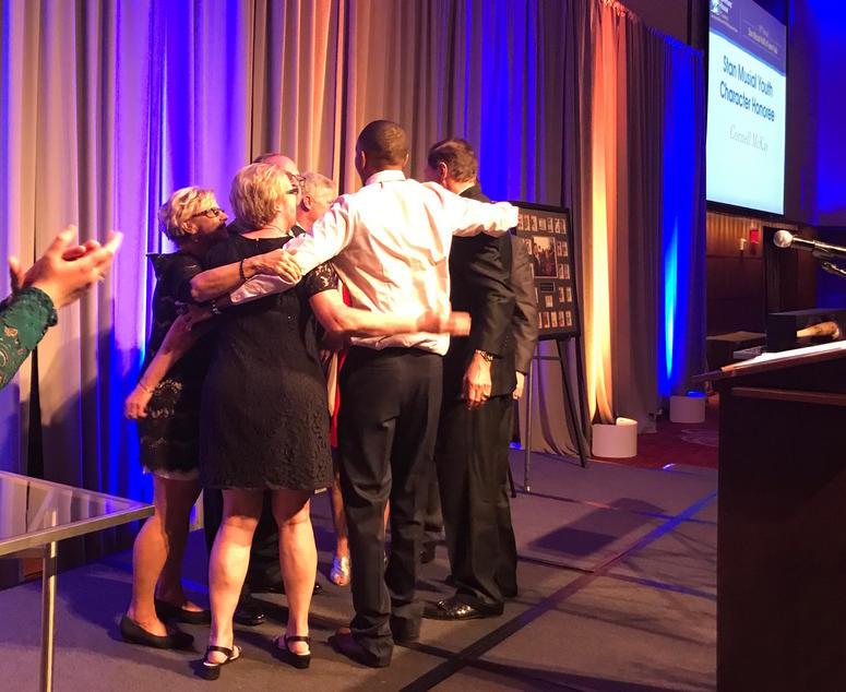 Cornell McKay hugging members of Stan Musial's family.