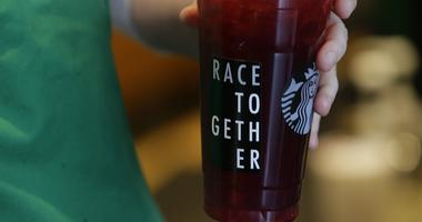 """Starbucks barista holds an iced tea drink with a """"Race Together"""" sticker"""