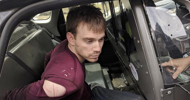 In this photo released by the Metro Nashville Police Department, Travis Reinking sits in a police car after being arrested in Nashville, Tenn., on Monday, April 23, 2018.