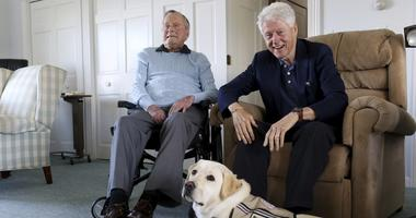 Former Republican President George H.W. Bush, left, and former President Bill Clinton, visiting Bush, pose for a photo with Sully, a yellow Labrador retriever who'll be Bush's first service dog at his home in Kennebunkport, Maine, Monday, June 25, 2018.