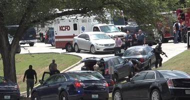 Authorities mobilize near 27th Street and Van Brunt Boulevard after three police officers were shot Sunday, July 15, 2018, in Kansas City, Mo., while trying to arrest a person of interest in the shooting death of a university student on July 6.