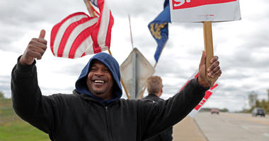 Bill Jackson, of St. Louis, gives a thumbs up to drivers that wave or honk as United Auto Workers outside the GM Wentzville Assembly Center in Wentzville, Mo., Wednesday, Oct. 16, 2019.