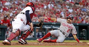 Washington Nationals' Adam Eaton (2) scores past St. Louis Cardinals catcher Yadier Molina