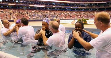 Three women wipe their faces after being batptized in a large swimming pool on the floor of the Dome at America's Center in St. Louis on Saturday August 17, 2019