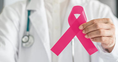 doctor holding pink ribbon representing breast cancer awareness