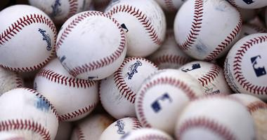 Basket of Rawlings baseballs sits on a practice field