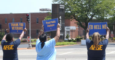 Federal workers hold signs and chant to passing cars outside of the Federal Center on Goodfellow Avenue on Saturday 27, 2019.