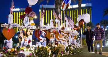 Visitors come to the makeshift memorial of 58 crosses near the Welcome to Las Vegas sign at 4:30 am Saturday, October 7, 2017.