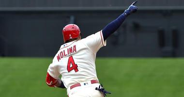 St. Louis Cardinals catcher Yadier Molina celebrates as he rounds 1st base.
