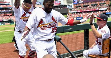 St. Louis Cardinals right fielder Dexter Fowler (25) is congratulated by second baseman Kolten Wong (16) and interim manager Mike Shildt