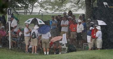 Fans look to seek shelter from the rain during a weather delay during the second round of the PGA Championship
