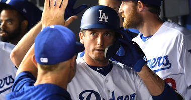 Los Angeles Dodgers third baseman David Freese (25) is greeted in the dugout