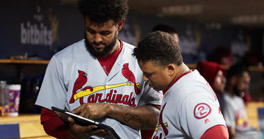 St. Louis Cardinals designated hitter Jose Martinez (38) and shortstop Yairo Munoz (34) look at an iPad