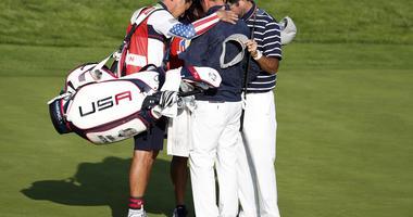 United States golfer Webb Simpson and United States golfer Bubba Watson huddle