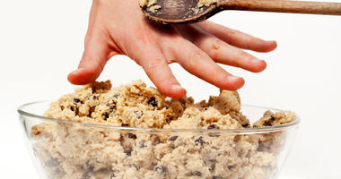 Hand reaching for raw cookie dough.