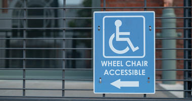 A handicap sign, wheel chair accessible logo pointing to left outdoor