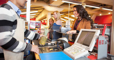 Cashier with customer in grocery store.