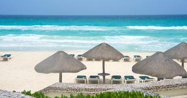 Cancun Mexico beach with beach chairs, white sand and sun