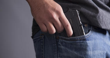 A man legally carries a firearm in his pocket for protection.