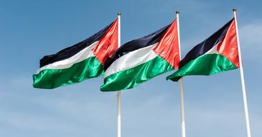 Three flags of Palestine waving in the sky