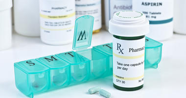 Daily medication dispenser with green prescription bottle and pills.