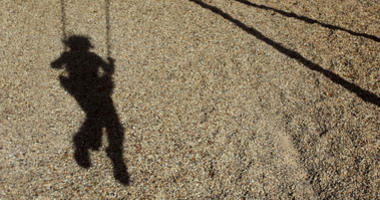 image of child swinging at the playground. Child is not visible, only the shadow of a child to represent lost or kidnapped children. Could be used for a drug ad to represent death. Stranger Danger.