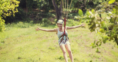 Happy smiling woman riding a zip line in a lush tropical forest while on family vacation. Arms spread wide showing her excitement