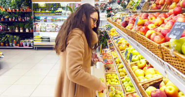 Woman selecting fresh red apples in grocery store produce department and putting it in plastic bag.