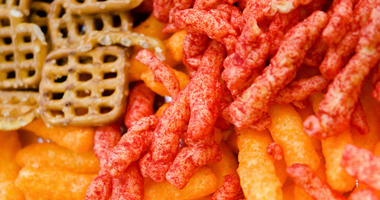 Close up shot of Cheese puffs, Colorful Cheetos and mini pretzels