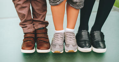 Three pairs of children`s feet wearing comfortable and fashion trainers.
